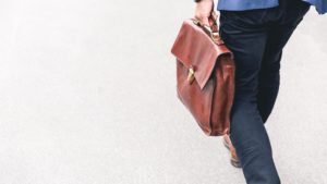 employee walking while carrying a briefcase