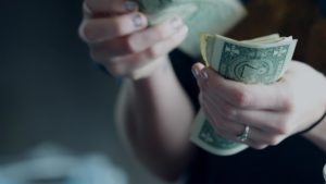 hands holding and counting dollar bills