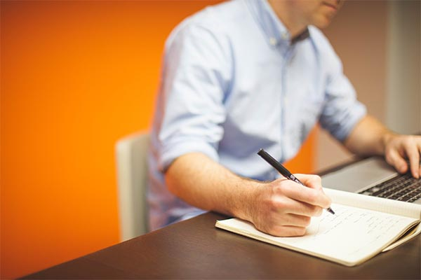 man writing in a notebook while using a laptop